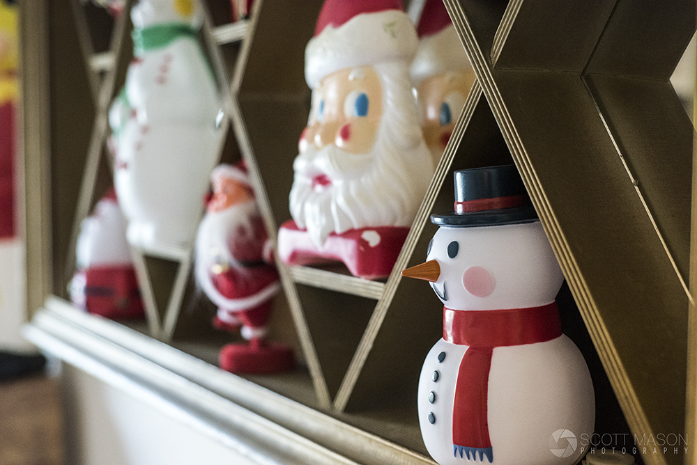 a close-up of a shelf with vintage snowmen and santa ornaments