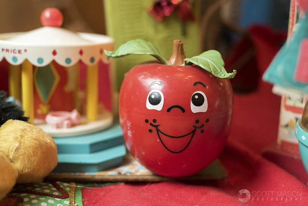 a small vintage apple ornament with a smiling face