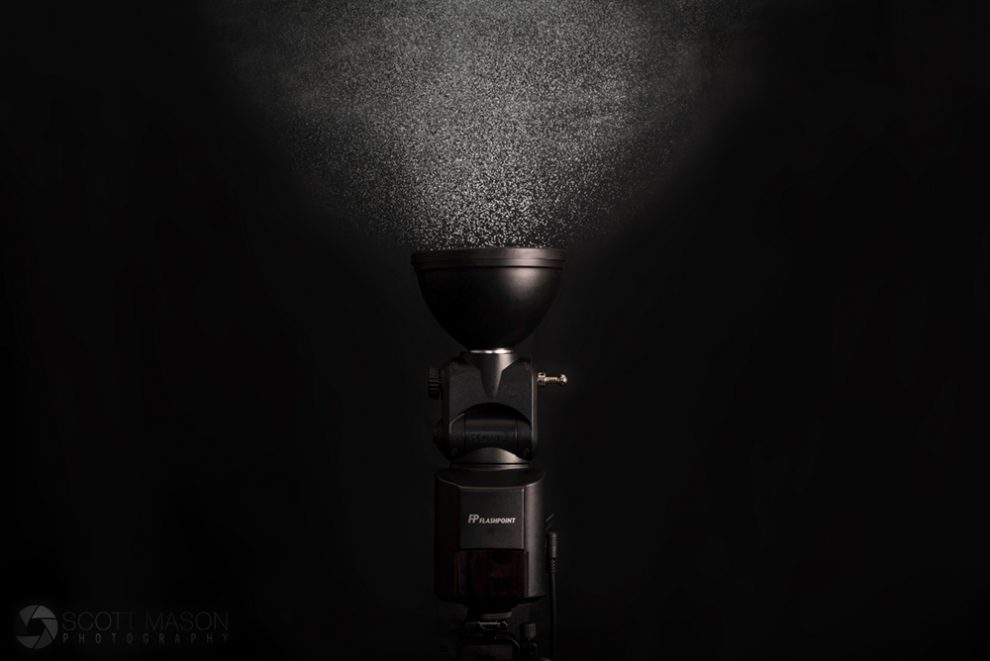 a studio product image of the streaklight 360 with a mist of water droplets rising from the flash