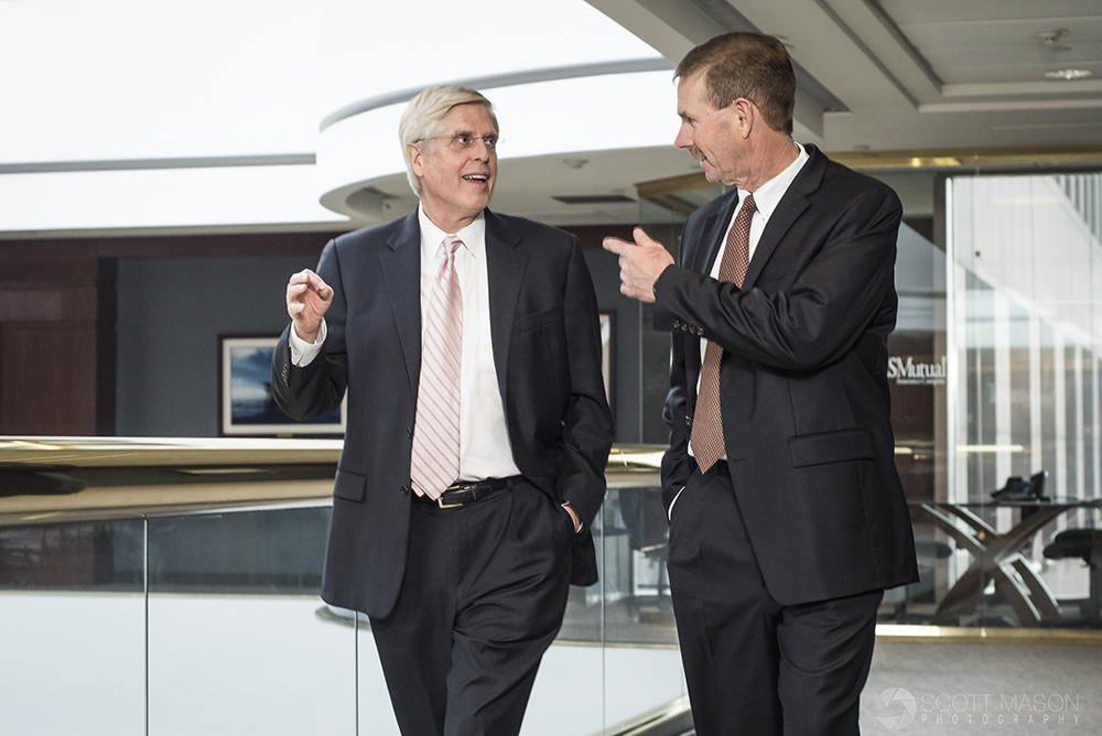 an editorial business photo of two men in suits walking and talking in an office hallway