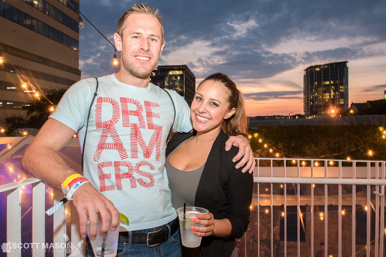 a photo of a couple standing on a deck with the sunset behind them, smiling at the camera