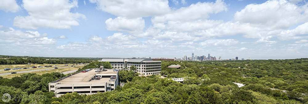 an elevated panoramic view of an office building and parking garage with downtown Austin behind it