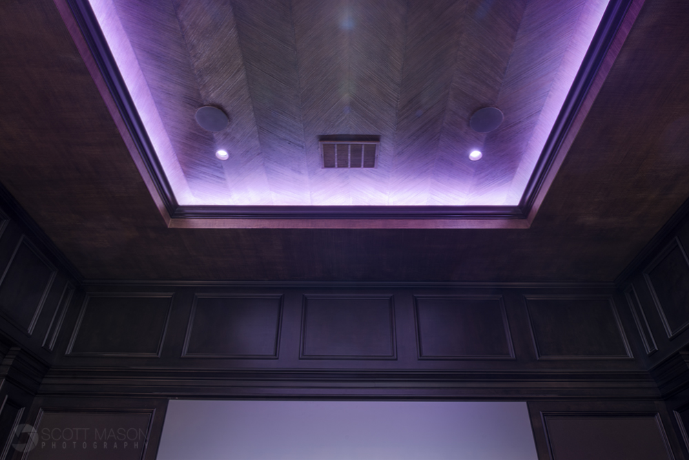 a recessed ceiling light in a home theater on a purple hue setting