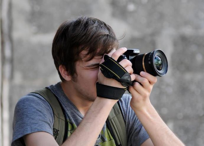 a young man taking pictures with a DSLR camera