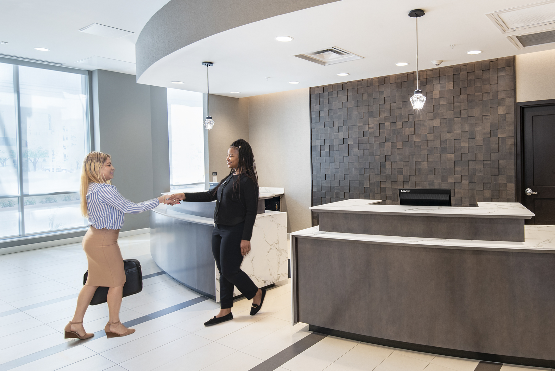 photo of a concierge greeting a guest in a hotel lobby