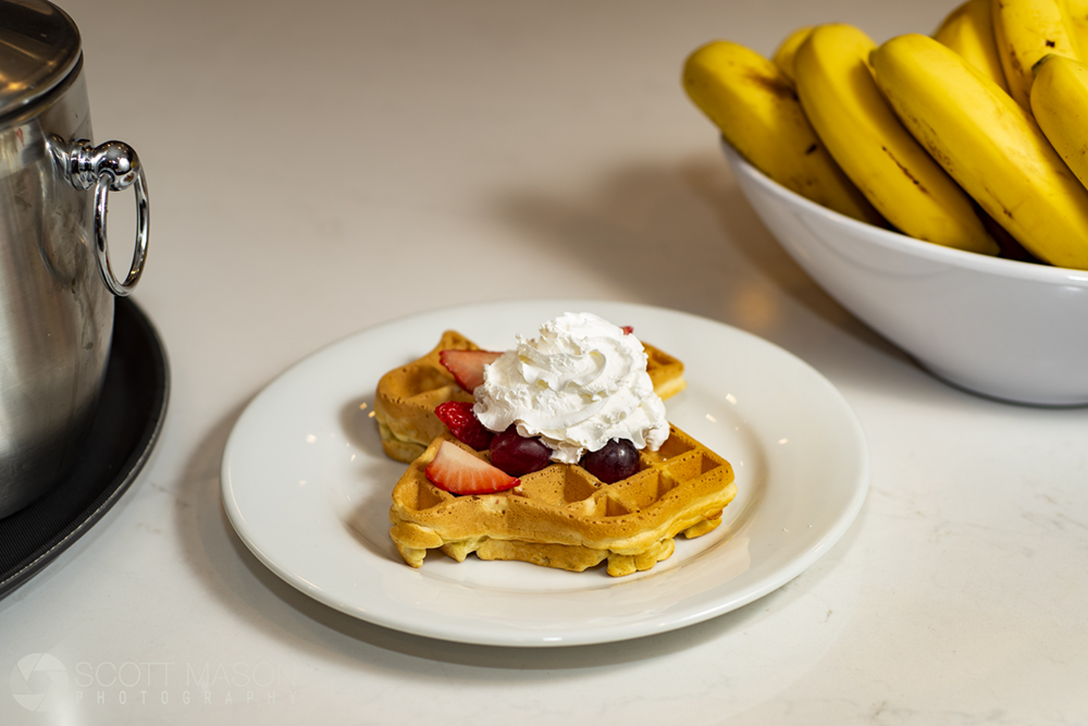 a photo of a texas-shaped waffle on a plate with whipped cream