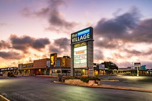 a strip mall at sunrise with a glowing monument sign