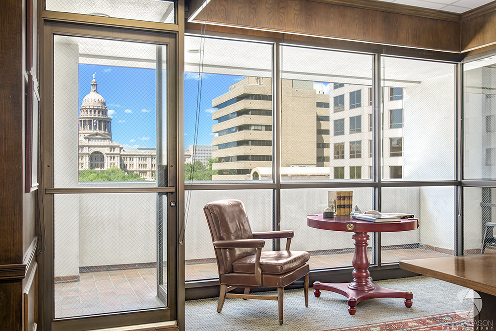 an interior window view of a lawyer's office with the Austin Capitol building in the background