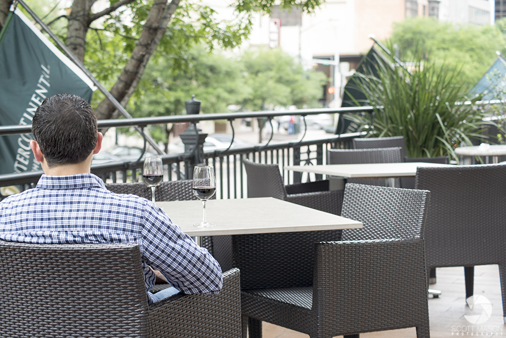 A lifestyle photo of a man sitting at a table drinking wine at the Stephen F Balcony in Austin Texas