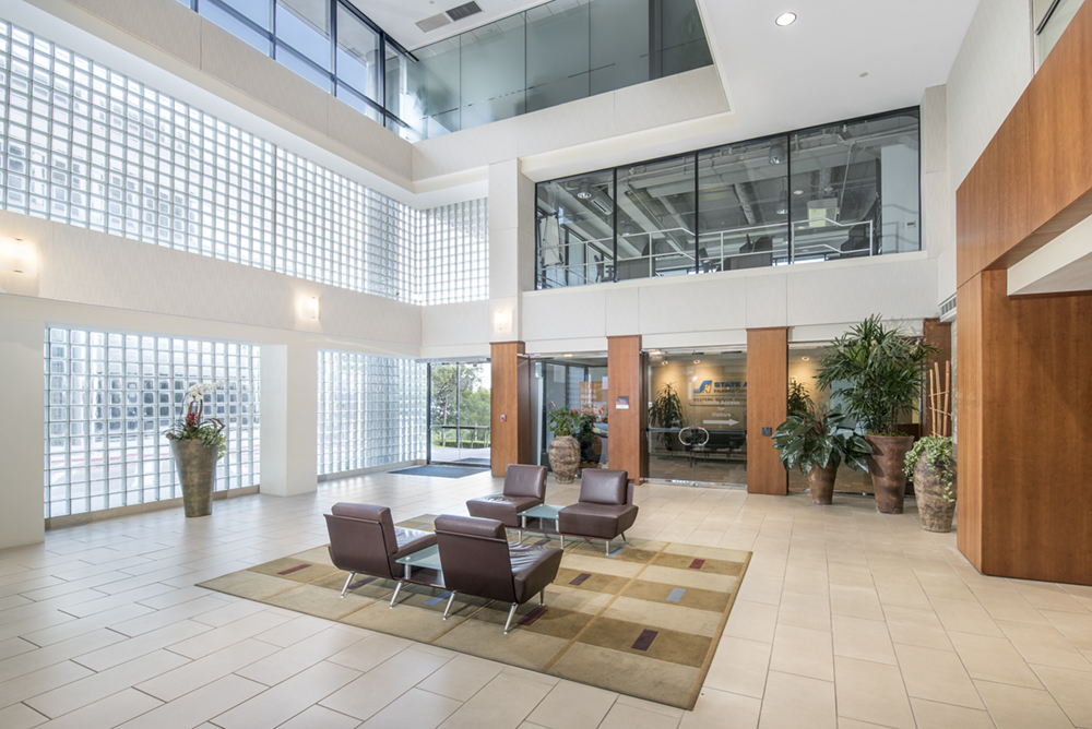 a large office lobby interior with furniture and a high vaulted ceiling